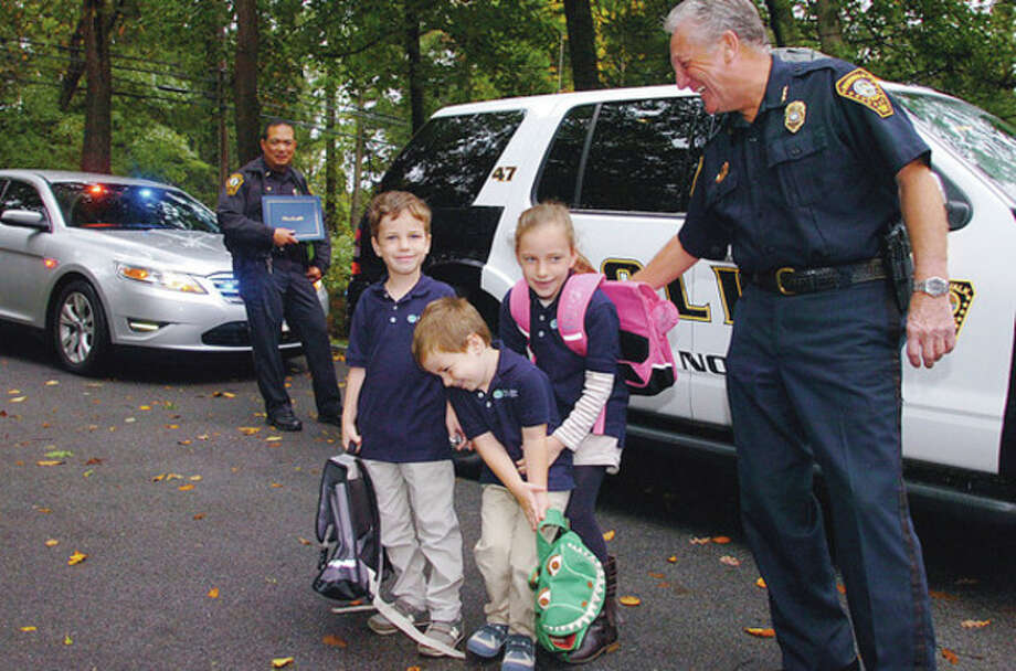 Norwalk Police Chief Rilling picks up the three Martyn children, Marius, Gaspard and Ciara, at their home to bring them to Side by Side Charter School Thursday morning. The special trip was won by the Martyn family as a unique auction item at the school's Annual Gala and Silent Auction last spring. Hour photo / Erik Trautmann / (C)2011, The Hour Newspapers, all rights reserved