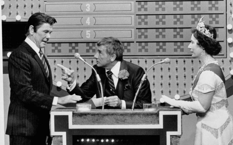 "FILE - In this Nov. 5, 1982 file photo provided by NBC-TV, ""Family Feud"" host Richard Dawson, center, gives President Reagan, played by ""Tonight Show"" host Johnny Carson, a chance at the big money as Queen Elizabeth (Rose Carr) readies herself at the buzzer during ""International Family Feud"" sketch on the show in Burbank, Calif. The ""feud"" pitted the Reagans against the Windsor family. Dawson, the wisecracking British entertainer who was among the schemers in the 1960s sitcom ""Hogan's Heroes"" and a decade later began kissing thousands of female contestants as host of the game show ""Family Feud"" died Saturday, June 2, 2012. He was 79. (AP Photo/NBC-TV, File) / AP1982"