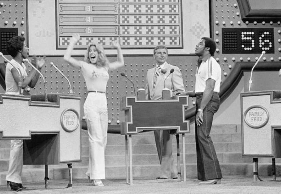 """FILE - In this June 25, 1980 file photo, as host Richard Dawson, center, watches, Dallas Cowboys running back Tony Dorsett, right, grimaces and Cowboys cheerleader Suzette Scholz-Derrick waves happily after Suzette beat Dorsett with a correct answer during taping of the """"Family Feud"""" game show at ABC television studios in Los Angeles. Five Cowboys footballers meet five Cowboys cheerleaders for week of competition on the popular daytime game show. Dawson, the wisecracking British entertainer who was among the schemers in the 1960s sitcom """"Hogan's Heroes"""" and a decade later began kissing thousands of female contestants as host of the game show """"Family Feud"""" died Saturday, June 2, 2012. He was 79. (AP Photo/Randy Rasmussen, File) / 1980 AP"""