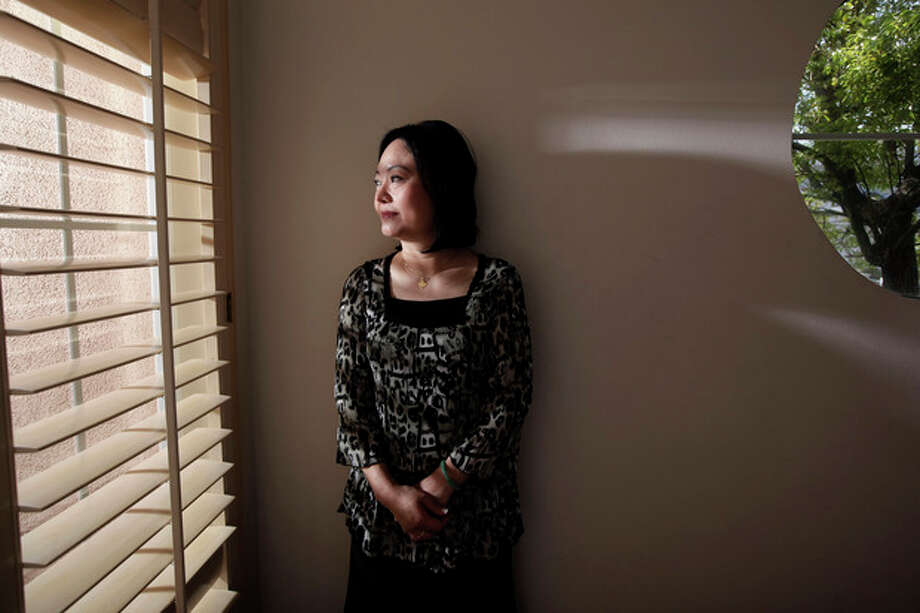 Phan Thi Kim Phuc stands by a window for a photo in Buena Park, Calif. on Saturday, June 2, 2012. It only took a second for Associated Press photographer Nick Ut to snap the iconic black-and-white image of her after a napalm attack in 1972. It communicated the horrors of the Vietnam War in a way words could never describe, helping to end one of America's darkest eras. But beneath the photo lies a lesser-known story. It's the tale of a dying child brought together by chance with a young photographer. A moment captured in the chaos of war that would serve as both her savior and her curse on a journey to understand life's plan for her. (AP Photo/Jae C. Hong) / AP