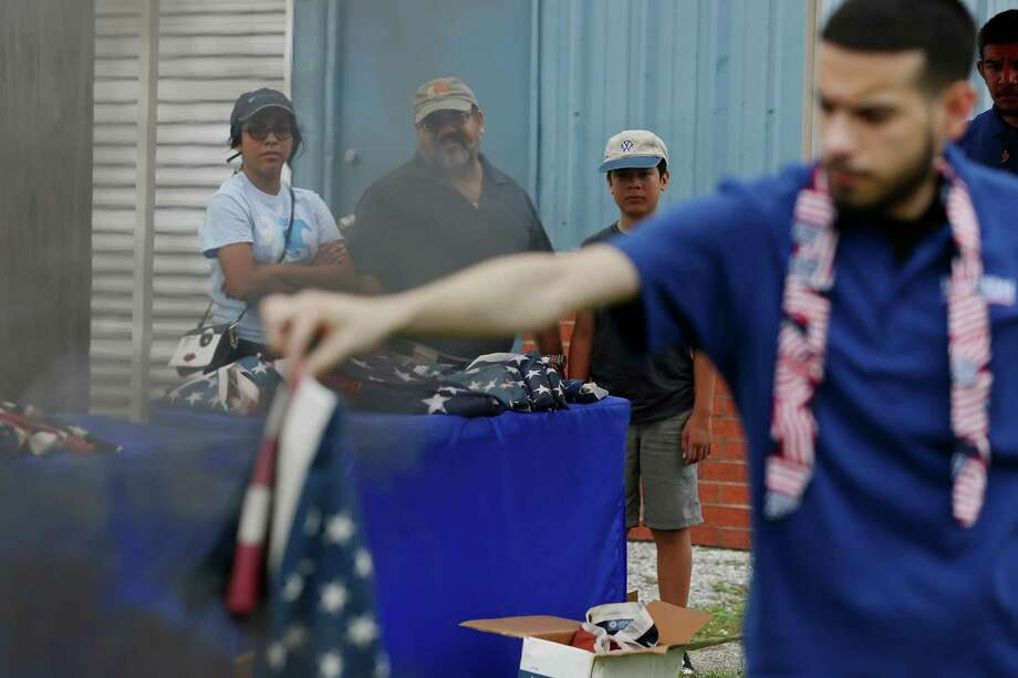 """Dean Arteaga, center and his family, Kioko, 14, and Roman, 11, watch as Dixie Flag Company employee Albert Munoz retires the family's U.S. flags during National Flag Day at the company, Tuesday, June 14, 2016. Dixie Flag has been provided the service on Flag Day since 1989. """"The best analogy is cremating of a loved one,"""" said Dixie Flag's President Henry """"Pete"""" Van de Putte, Jr. on the tradition of retiring the U.S. flag. Photo: JERRY LARA, Staff / San Antonio Express-News / © 2016 San Antonio Express-News"""