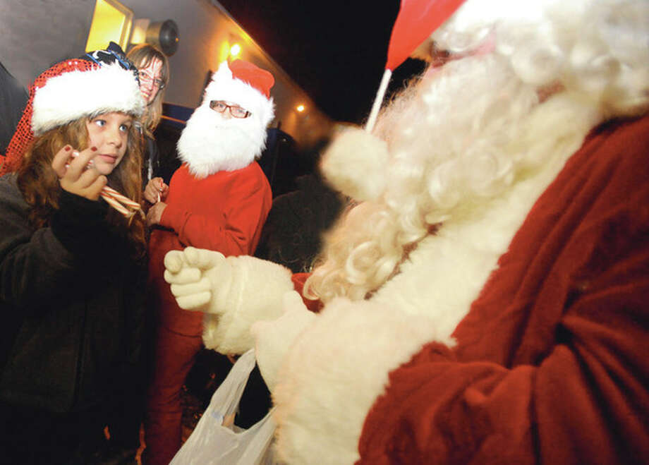 Hour photo/Matthew Vinci Lily Motyka 10, gets in first for a candy cane from Santa, Sunday at the Norwalk American Legion Post 12 Christmas tree lighting. / (C)2011, The Hour Newspapers, all rights reserved