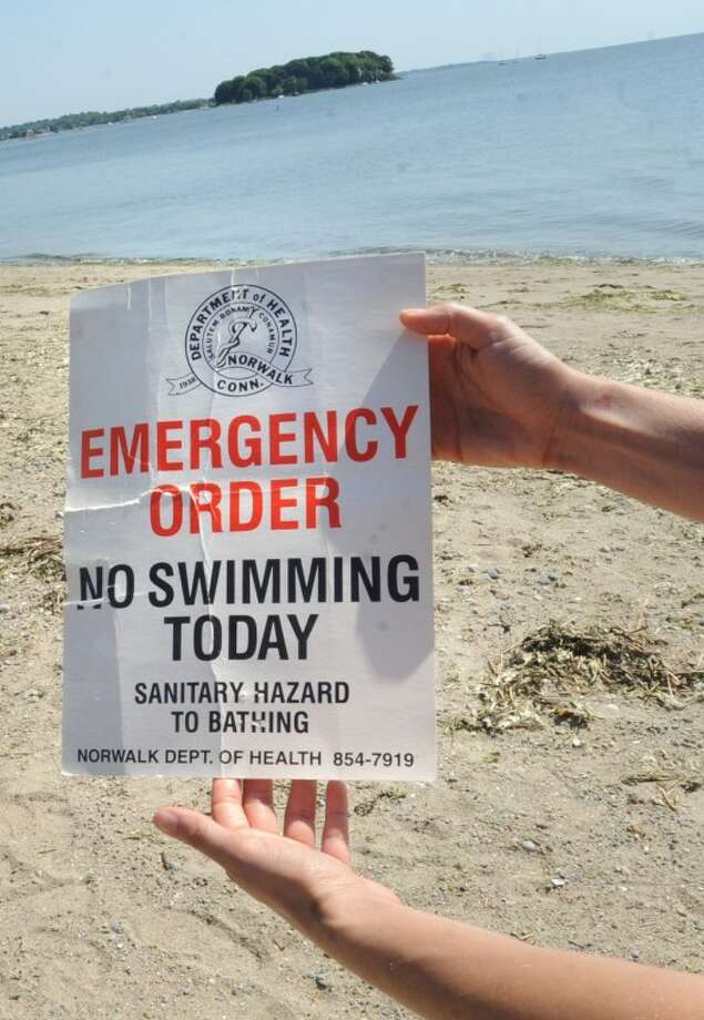 A life guard at Calf Pasture Beach prepeares a no swimming sign Sunday because of debris concerns. hour photo/Matthew Vinci