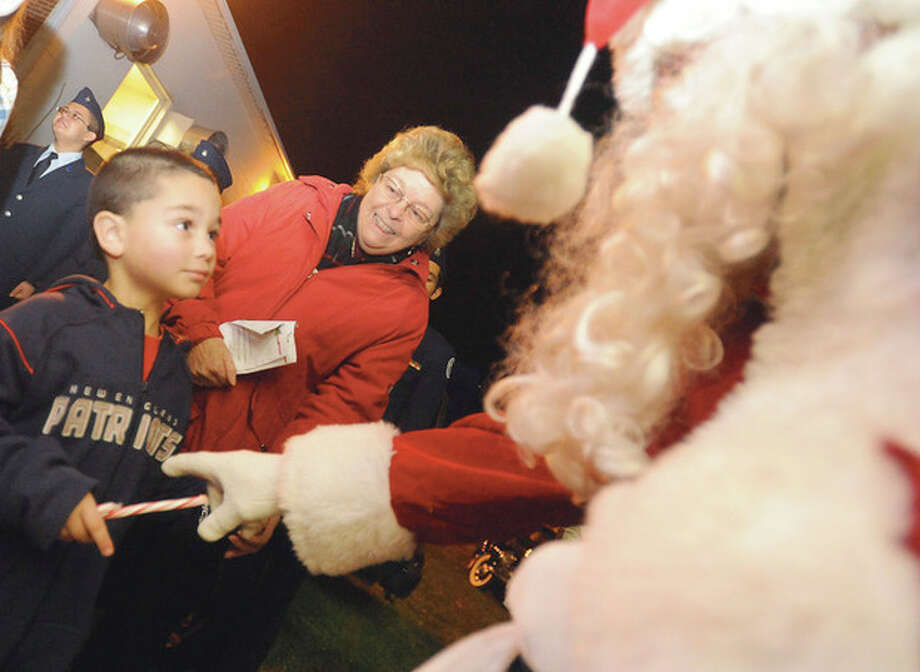 Michael Rossi 4, with his grandmother Marcia Rossi gets a candy cane from Santa Sunday at the Norwalk Post 12 Christmas tree lighting, hour photo/Matthew Vinci / (C)2011, The Hour Newspapers, all rights reserved