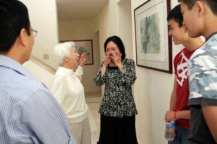 Phan Thi Kim Phuc, center right, wipes her eyes as she introduces Dr. My Le, who treated Kim Phuc in Vietnam two days after a napalm attack in Vietnam on June 8, 1972, to her two sons, Thomas, second from right, and Stephen Bui, right, during a reunion in Buena Park, Calif. on Saturday, June 2, 2012. It only took a second for Associated Press photographer Nick Ut to snap the iconic black-and-white image of her after the attack 40 years ago. It communicated the horrors of the Vietnam War in a way words could never describe, helping to end one of America's darkest eras. But beneath the photo lies a lesser-known story. It's the tale of a dying child brought together by chance with a young photographer. A moment captured in the chaos of war that would serve as both her savior and her curse on a journey to understand life's plan for her. (AP Photo/Jae C. Hong) / AP