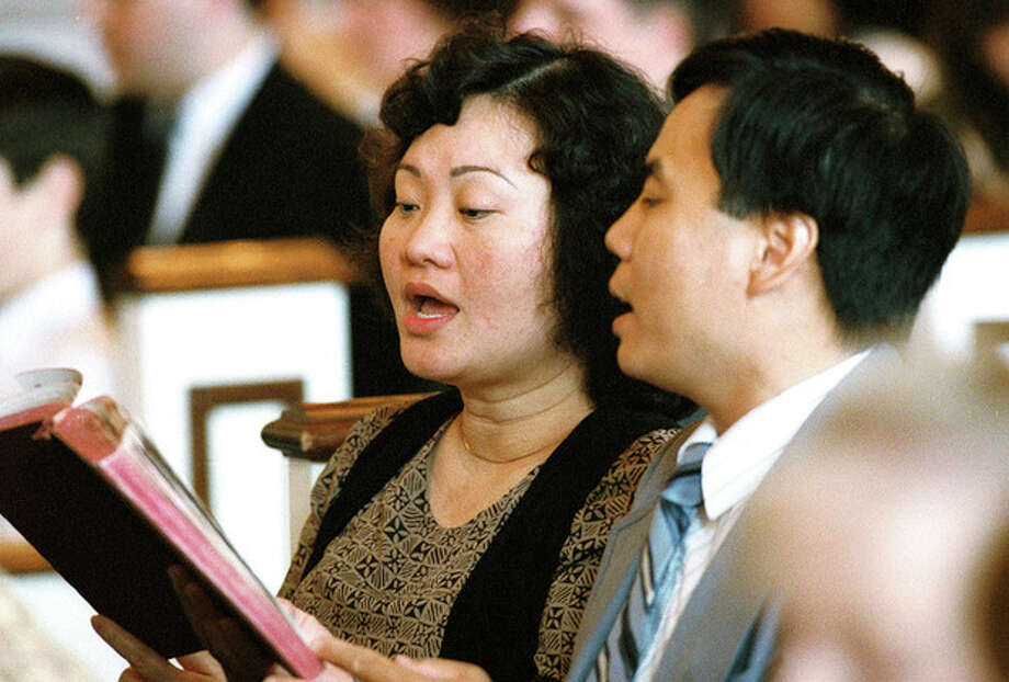 FILE - In this May 25, 1992 file photo, Phan Thi Kim Phuc and her husband, Bui Huy Toan, sing during a service at the Faithway Baptist Church in Ajax, Ontario, Canada. The couple met in Cuba where Kim Phuc was sent from Vietnam to study in 1986. Phuc, who was the main subject in Associated Press photographer Nick Ut's iconic image of the aftermath of a June 8, 1972 napalm attack in Vietnam, was granted political asylum in Canada in 1992. (AP Photo/Nick Ut) / AP1992