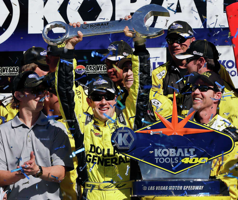 Driver Matt Kenseth holds up the trophy as the celebrates in Victory Lane after winning the NASCAR Sprint Cup Series auto race, Sunday, March 10, 2013 in Las Vegas. (AP Photo/Julie Jacobson) / AP