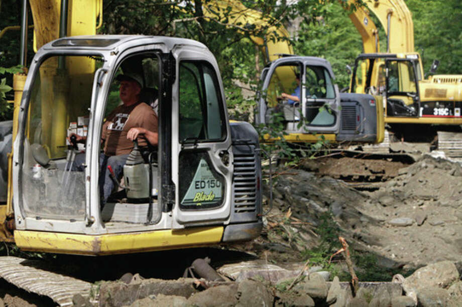 Excavators line up to re-dig the stream bed near Camp Brook Rd. on Wednesday, Aug. 31, 2011 in Bethel, Vt. About 2 million people remained without power in water-logged homes and businesses from North Carolina through New England, where hurricane-turned-tropical-storm Irene has been blamed for at least 45 deaths in 13 states. (AP Photo/Toby Talbot) / AP