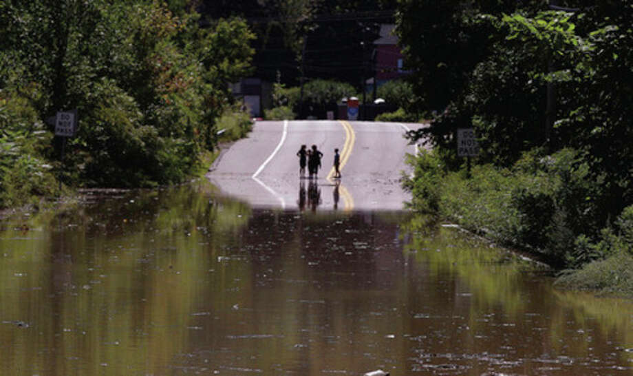 Children stand on the far side of a flooded portion of Massachusetts Rt. 5 which is closed to traffic in Northhampton, Mass., Monday afternoon, Aug. 29, 2011 due to flooding from tropical storm Irene. (AP Photo/Stephan Savoia) / AP