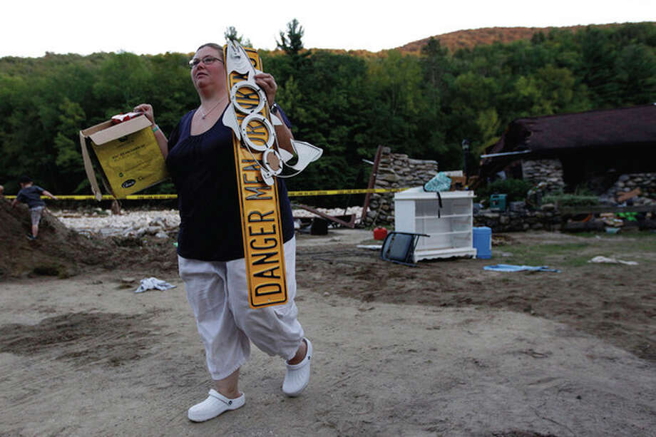Jillianne Davis, who's home was destroyed by floodwaters rustling from Tropical Storm Irene, salvages possessions, Tuesday, Aug. 30, 2011, in Woodford, Vt. (AP Photo/Matt Rourke) / AP
