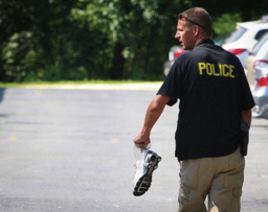 A New Castle County Police officer carries a shoe recovered from a wooded area near Lantana Square shopping center in Hockessin, Del. on Monday, Aug. 29, 2011 after search teams found the bodies of two men who decided to sprint through Hurricane Irene during the peak of the storm Saturday night. (AP Photo/The Wilmington News-Journal, Suchat Pederson) NO SALES / The News Journal-2011