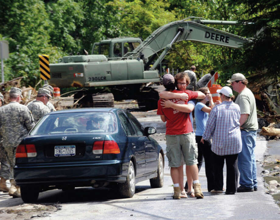 Members of the Quinn family ,right, embrace outside their home while members of the New York National Guard 204th Engineer Battalion , 827 Engineering company from Binghamton, N.Y., use heavy equipment to clear debris from a stream that destroyed their family printing business on Mill Valley Rd caused by Tropical Storm Irene in Middleburgh, N.Y., Tuesday, Aug. 30, 2011. (AP Photo/Hans Pennink) / Hans Pennink