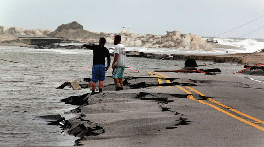 Telephone workmen attempt to find the telephone line along the storm battered road on Hwy 12 in Rodanthe, N.C. Tuesday, Aug. 30, 2011. Landline phone service and power had been restored to Hatteras Village, Frisco, Buxton and Avon but north towards Pea Island damage was severe and residents were still disconnected Tuesday. ( AP Photo/The News & Observer, Chuck Liddy) MANDATORY CREDIT / 2011 The News & Observer