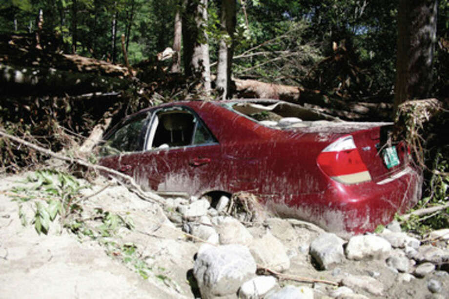A car sits submerged in mud, rocks and fallen trees on what was once Dover Road in Williamsville, Vt., during severe flooding from Tropical Storm Irene Tuesday, Aug. 30, 2011. (AP Photo/The Brattleboro Reformer, Zachary P. Stephens) MANDATORY CREDIT / Brattleboro Reformer