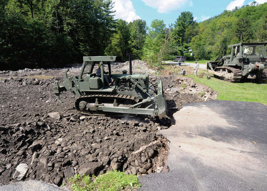 Members of the New York National Guard 204th Engineer Battalion , 827 Engineering company from Binghamton, N.Y., use heavy equipment to rebuild a stream bank on Mill Valley Rd damaged by Tropical Storm Irene in Middleburgh, N.Y., Tuesday, Aug. 30, 2011. (AP Photo/Hans Pennink) / Hans Pennink