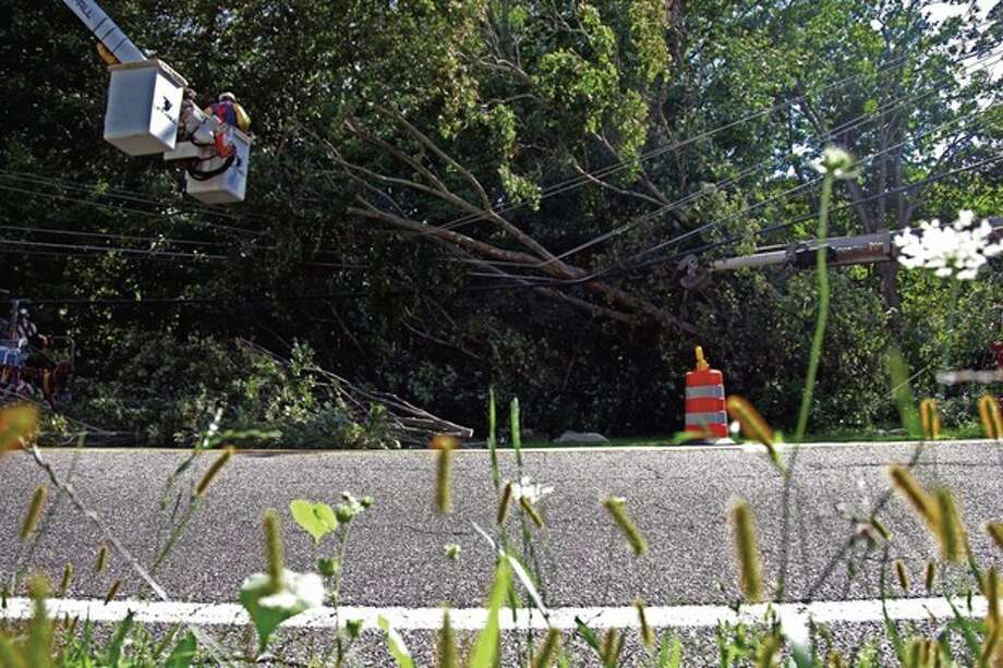 Workers remove a tree downed on a power line, in Sparta, N.J., Monday, Aug. 29, 2011. Many Sparta residents have been without power since Sunday due to downed power lines from Irene. (AP Photo/Chelsea Matiash) / AP