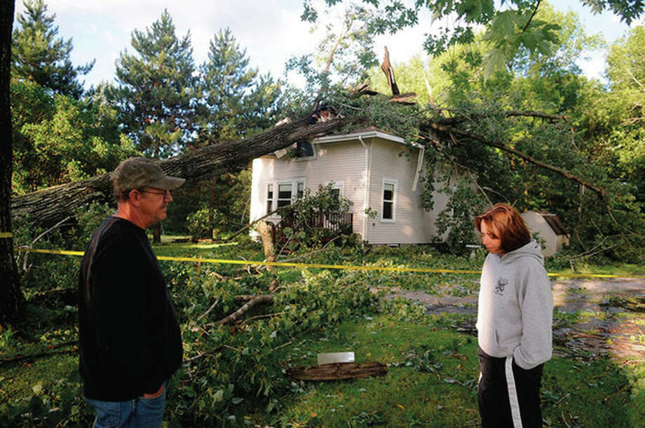 Bernard Hallowell and his wife, Kim, survey the damage Monday, Aug. 29, 2011, to their Monmouth, Maine home after it was struck by a tree Sunday during Tropical Storm Irene. The couple and their dog escaped injury. (AP Photo/The Kennebec Journal, Andy Molloy) / The Kennebec Journal