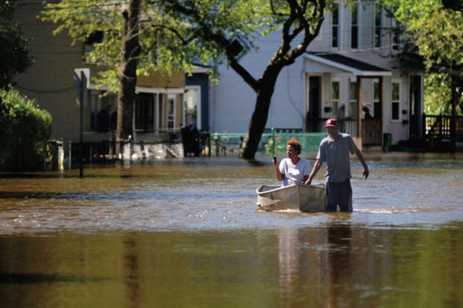 Greg Walker pulls a woman, who wished not to be identified, with his canoe north on Winnikee Ave. in Poughkeepsie, N.Y. after the Fallkill Creek flooded large areas in the north side of the city Monday, Aug. 29, 2011. Tropical Storm Irene left stunned upstate New Yorkers shaking their heads Monday at a crippling wallop they never thought possible: Cars and trucks tossed like toys, houses torn from their foundations, trees tumbling down roiling, muddy rivers like matchsticks and roads shredded by raging torrents. (AP Photo/The Journal, Spencer Ainsley) / Poughkeepsie Journal