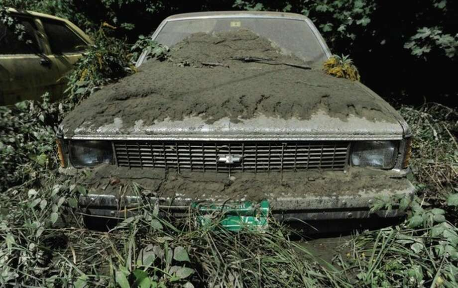 A parked car is seen covered in mud along Route 9 in the aftermath of Tropical Storm Irene, in Brattleboro, Vt., Tuesday, Aug. 30, 2011. (AP Photo/Jessica Hill) / AP2011