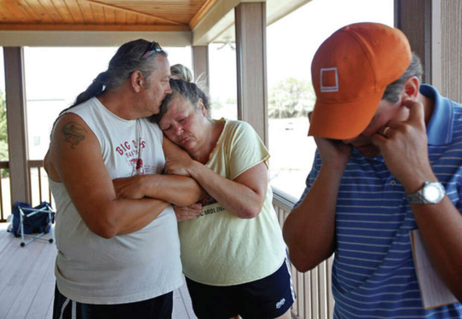 Standing on a neighbors porch in Stumpy Point, N.C., Darnel and Debbie Talbert lean on each other as Nationwide insurance agent Paul Tine checks on information concerning their policy on Tuesday, Aug. 30, 2011. The Talbert's house was heavily damaged by Hurricane Irene. (AP Photo/The News & Observer, Shawn Rocco) / Copyright 2011 The Associated Press. All rights reserved. This material may not be published, broadcast, rewritten or redistributed.