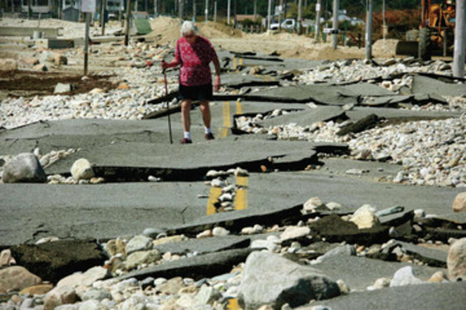 Pat Richard tries to make her way along what remains of East Beach Road in Westport, Mass., Wednesday, Aug. 31, 2011. The beach-front road was shattered by high surf and winds when Tropical Storm Irene swept the area on Sunday. (AP Photo/The Standard Times, Peter Pereira) / PETER PEREIRA