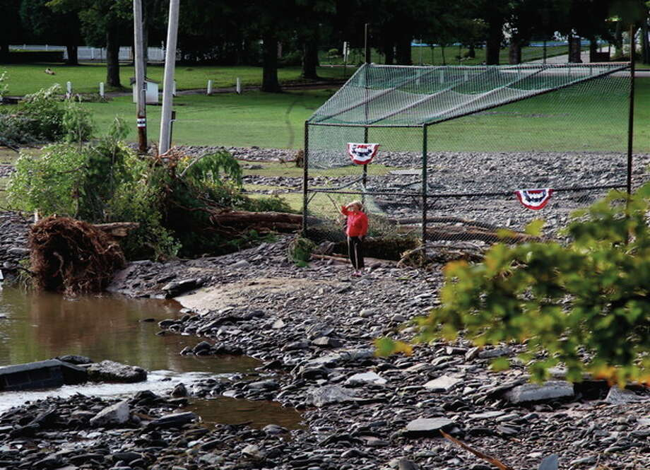 A woman looks at the damage in Fleishmanns N.Y. Tuesday, Aug. 30, 2011. The small resort town was torn apart by rushing waters in the aftermath of Tropical Storm Irene. Officials in staggering communities and in Albany are starting to look back at what else they could have done to better brace for Tropical Storm Irene, which surprisingly devastated swaths of upstate. (AP Photo/Robert Ray) / AP