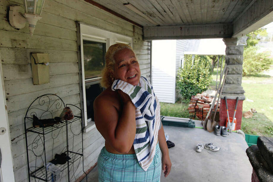 Nancy Gonzalez wipes the sweat from her face as she stands outside her home in New Bern, N.C., Monday, Aug. 29, 2011 . Hundreds of thousands of North Carolina residents continued a slow cleanup Monday in the wake of Hurricane Irene while some remained in shelters and thousands were still without power. (AP Photo/Chuck Burton) / AP