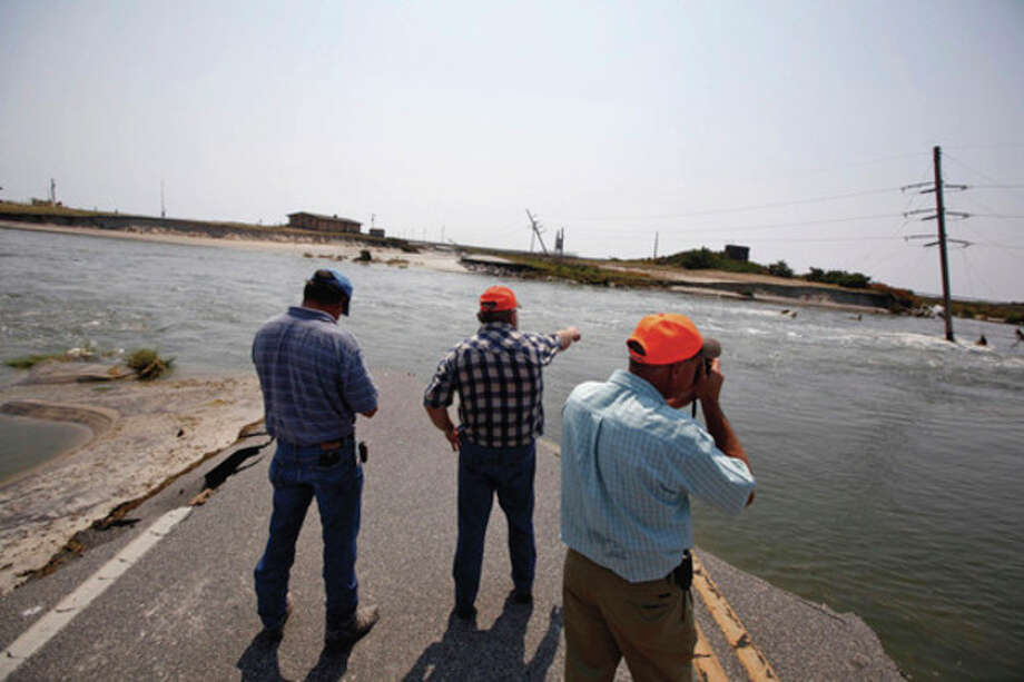 N.C. Dept. of Transportation officials Randy Boyd, left, Jerry Lindsey and Donald Lee stand on the edge of a washed out N.C. 12 about 8-miles south of the Bonner Bridge in the Pea Island National Wildlife Refuge on the Outer Banks of N.C. on Monday, August 29, 2011. They and a contract survey crew came down to assess the numerous breaches caused by Hurricane Irene. (AP Photo/The News & Observer, Shawn Rocco) / 2011, The News & Observer
