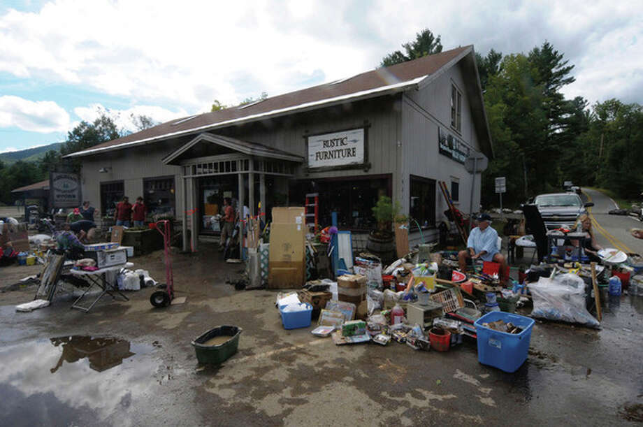 Family and friends help clean up the mud damage to McDonough'd Valley Hardware Co. caused by Tropical Storm Irene in Keene Valley, N.Y., Monday, Aug. 29, 2011. (AP Photo/Hans Pennink) / Hans Pennink