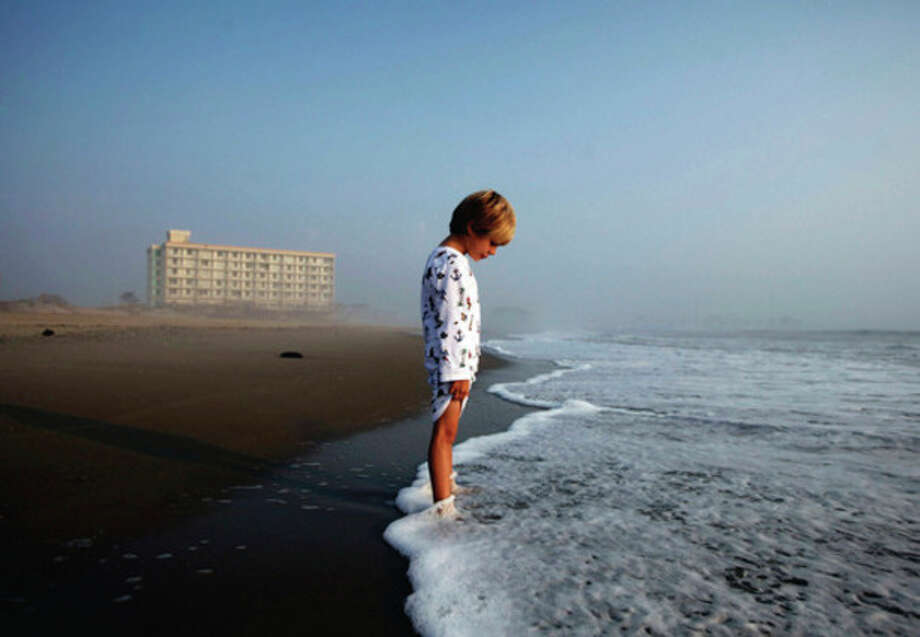 Jack Camper, 4, watches as the ocean rises over his feet at Nags Head, N.C. on Monday, Aug. 29, 2011. Traveling from Roanoke, Va., he and his family were staying in the Comfort Inn South, right behind him, as they waited for word from their realtor on whether they could head to their beach house rental in Corolla, N.C. following Hurricane Irene. (AP Photo/The News & Observer, Shawn Rocco) / 2011, The News & Observer