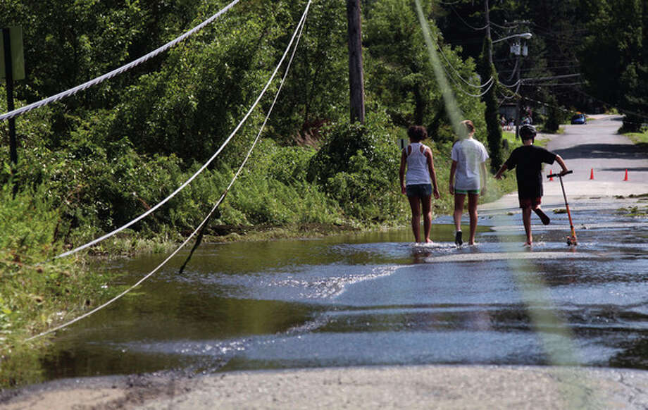 Gabby Caselnova, 13, left, Jessica Burns, 13, center, and Andrew Caselnova, 10, walk through floodwaters under downed power lines at Sparta Lake in Sparta, N.J., Monday, Aug. 29, 2011. They have been without power since Sunday due to downed power lines from Hurricane Irene. (AP Photo/Chelsea Matiash) / AP