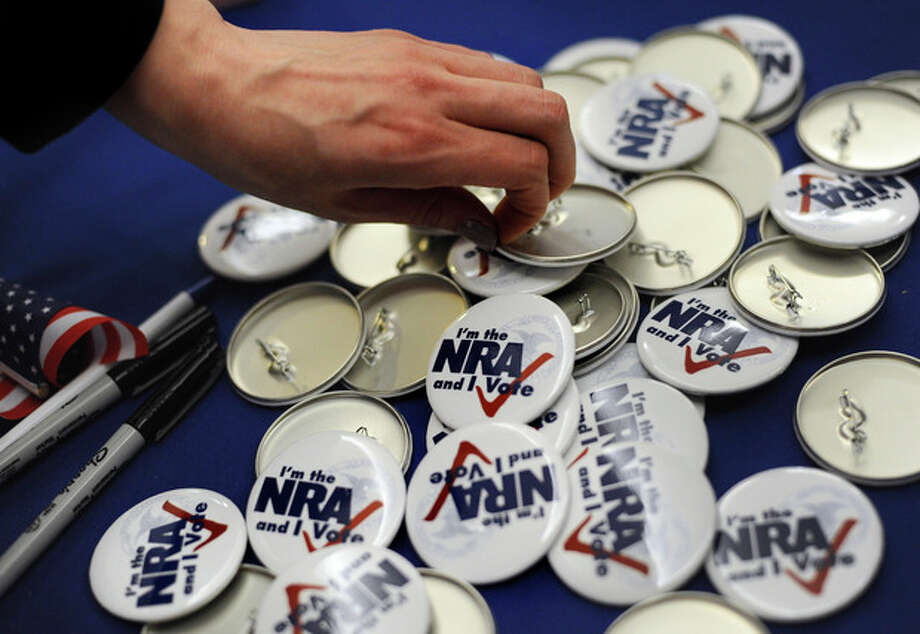 "A woman grabs a button during a ""lobby day"" held by the National Rifle Association and other gun rights groups at the Legislative Office Building in Hartford, Conn., Monday, March 11, 2013. Both sides of the gun control issue are increasing pressure on Connecticut lawmakers who are close to voting on changes to state law stemming from the deadly shooting at Sandy Hook Elementary School in Newtown. (AP Photo/Jessica Hill) / FR125654 AP"