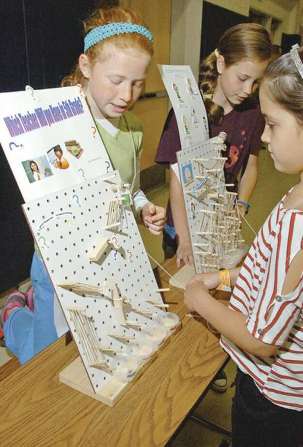 Cider Mill Elementary School 5th graders Mary Colias demonstrates her invention to Lorelei Marcell during the school's annual Invention Convention Friday.Hour photo / Erik Trautmann