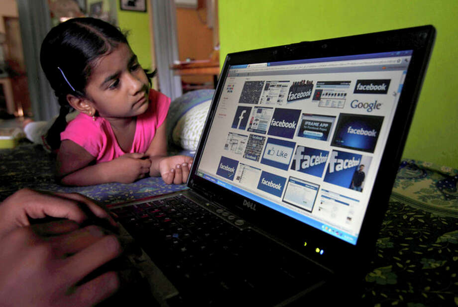 FILE- In this Friday, May 18, 2012, file photo, a child looks at a laptop displaying Facebook logos in Hyderabad, India. Facebook said Monday, June 4, 2012, it is testing out ways to allow younger kids on its site without needing to lie. (AP Photo/Mahesh Kumar A., File) / AP2012