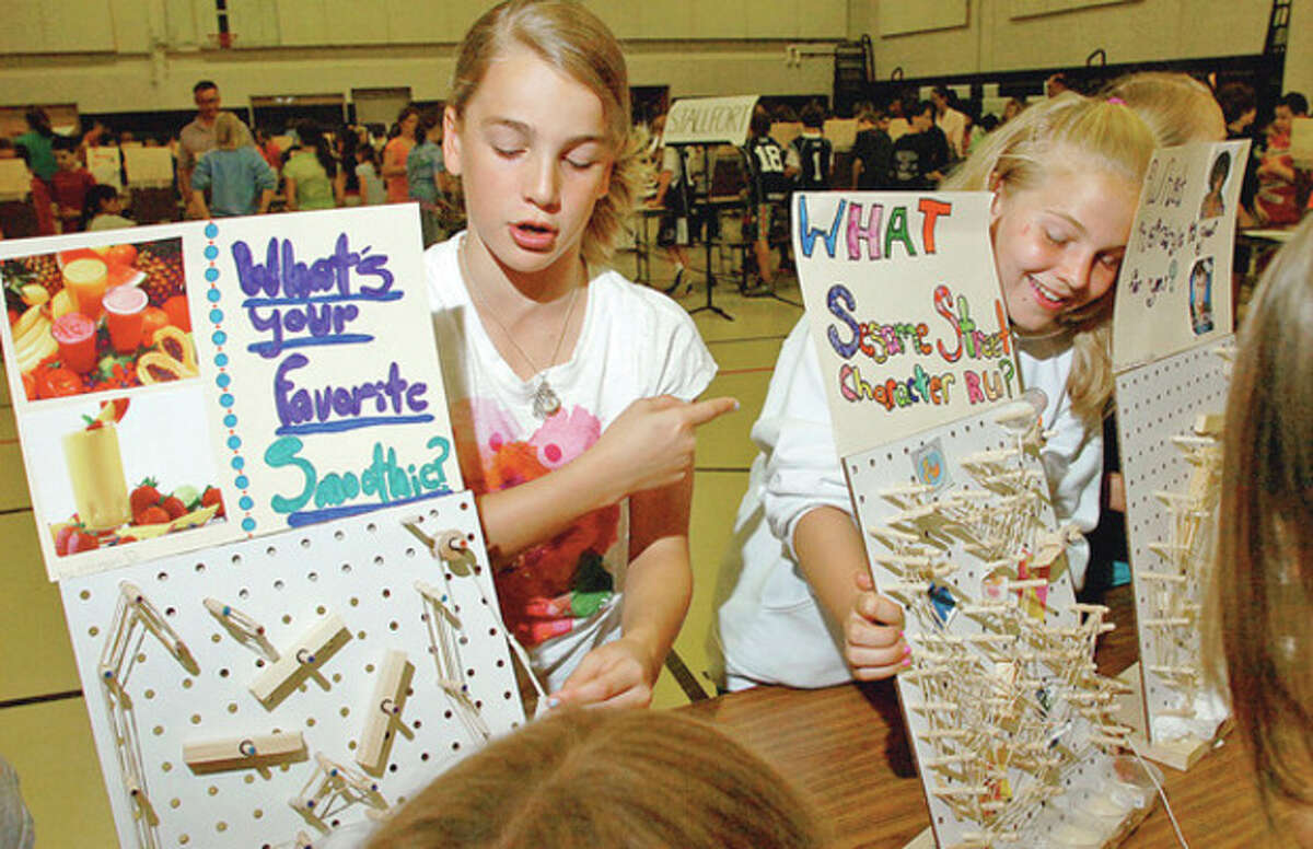 Cider Mill Elementary School 5th gradersMoragn Dill and Sara Wiltshire demonstrate their inventions during the school's annual Invention Convention Friday. Hour photo / Erik Trautmann