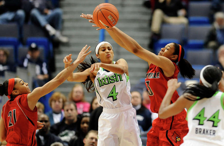 Notre Dame's Skylar Diggins (4) passes the ball between Louisville's Bria Smith (21) and Sheronne Vails (3) to teammate Ariel Braker (44) in the first half of an NCAA college basketball game in the semifinals of the Big East Conference tournament in Hartford, Conn., Monday, March 11, 2013. (AP Photo/Jessica Hill) / FR125654 AP