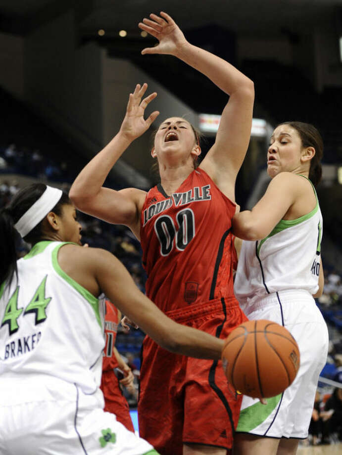 Louisville's Sara Hammond (00) has the ball knocked away by Notre Dame's Ariel Braker (44) as Natalie Achonwa, right, defends in the first half of an NCAA college basketball game in the semifinals of the Big East Conference tournament in Hartford, Conn., Monday, March 11, 2013. (AP Photo/Jessica Hill)