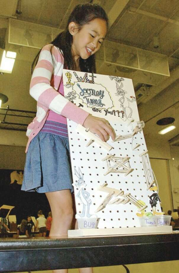 Cider Mill Elementary School 5th grader Charlotte Rigby demonstrates her invention during the school's annual Invention Convention Friday.Hour photo / Erik Trautmann