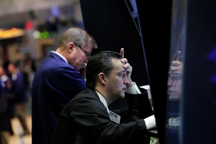 Trader Theodore Nelson, right, is reflected on a panel as he works on the floor of the New York Stock Exchange Monday, June 4, 2012. The Dow Jones industrial average opened at its lowest level since December after a 275-point sell-off on Friday caused by grim economic signals, especially a dismal report on the U.S. labor market. (AP Photo/Richard Drew) / AP