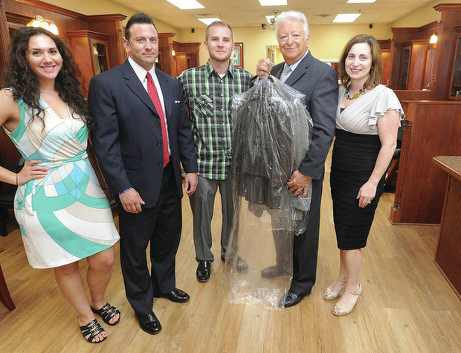 Hour photo / Matthew VinciMayor Richard A. Moccia, second from right, donates a suit to the donation drive for Save a Suit at Roosters Men's Grooming Center in Norwalk. Shown with the mayor are, from left, Roosters staff Jessica Ewud, Scott Sokolowski, Adam Grondin and Maria Raduazzo, the owner of Roosters Men's Grooming Center.