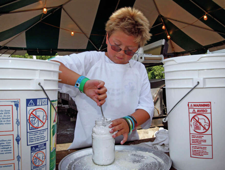 T.J. Boyrer, 11, prepares cheese for pizza fritta during the annual St. Ann's Festival in Norwalk Saturday afternoon.