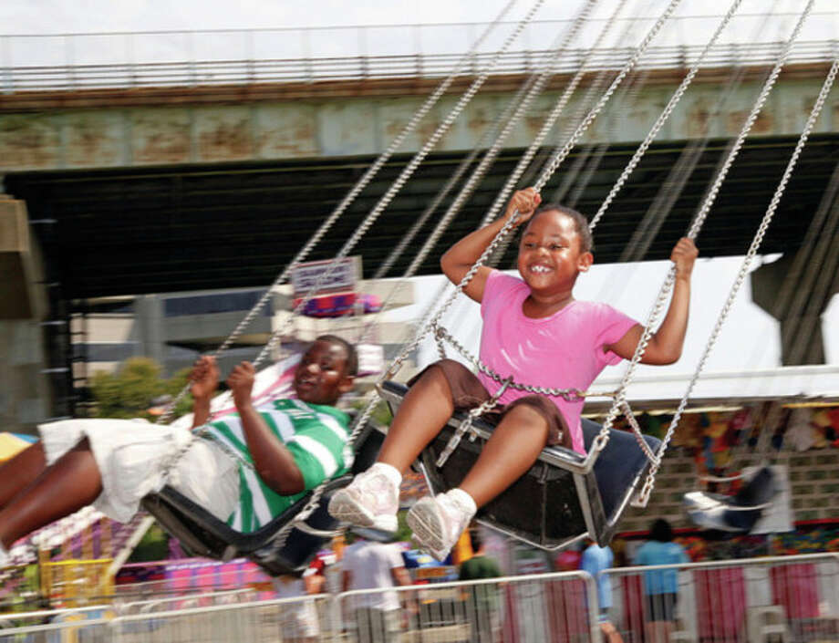 Adrianna Richardson, 5, and her brother Marques, 12, enjoy a ride during the annual St. Ann's Festival in Norwalk Saturday afternoon.