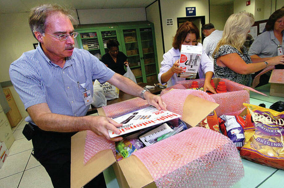 Hour Photo/Alex von Kleydorff. Norden Systems Program Manager Guido Sottosanti finishes packing one of the many boxes the employees have donated and will ship to Norwalk troops in the Adopt A Platoon Program. / 2011 The Hour Newspapers