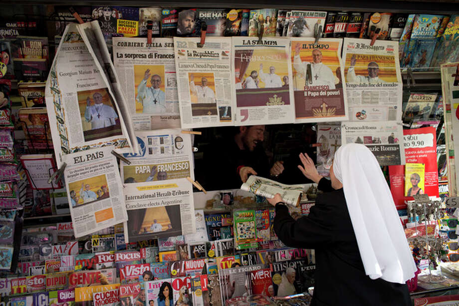 A nun buys a newspaper with the front page of Pope Francis, at a newsstand in Rome Thursday, March 14, 2013. Argentine Cardinal Jorge Mario Bergoglio, who chose the name of Pope Francis, was elected the 266th pontiff of the Roman Catholic Church on Wednesday, March 13, 2013, at the Vatican. (AP Photo/Oded Balilty) / AP