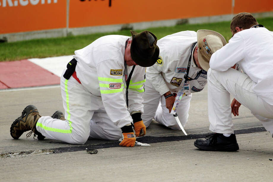 Crew members look over the asphalt patch on the road course during IndyCar's Detroit Grand Prix auto race on Belle Isle in Detroit, Sunday, June 3, 2012. The race was red flagged 63 minutes into the race because of the road condition. (AP Photo/Carlos Osorio) / AP