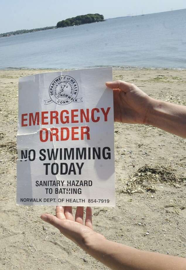 Hour photo / Matthew VinciA lifeguard at Calf Pasture Beach prepares a no swimming sign Sunday because of sanitary hazards caused by sewage runoff.