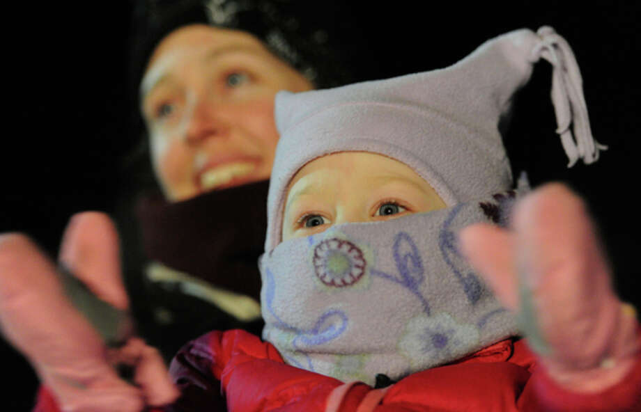 Mitch Seavey's granddaughter Annie Seavey, 2, being held by her mother Jen, cheers under the burled arch in Nome on Tuesday evening, March 12, 2013. (AP Photo/The Anchorage Daily News, Bill Roth) LOCAL TV OUT (KTUU-TV, KTVA-TV) LOCAL PRINT OUT (THE ANCHORAGE PRESS, THE ALASKA DISPATCH) / The Anchorage Daily News