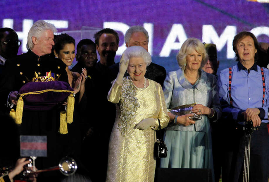 From right, Sir Paul McCartney and Camilla, Duchess of Cornwall join onstage Britain's Queen Elizabeth II, centre, as she waves to spectators at the end of the Queen's Jubilee Concert in front of Buckingham Palace, London, Monday, June 4, 2012. The concert is a part of four days of celebrations to mark the 60 year reign of Britain's Queen Elizabeth II. (AP Photo/Joel Ryan) / AP