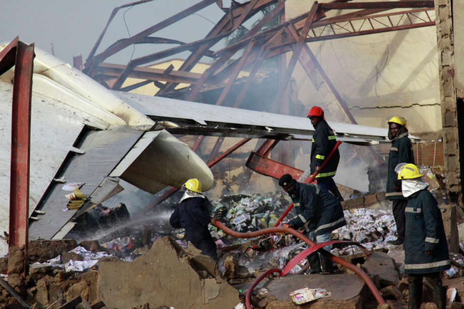 Rescue workers search for bodies at the site of a plane crash in Lagos, Nigeria, Monday, June 4, 2012. A passenger plane carrying more than 150 people crashed in Nigeria's largest city on Sunday, government officials said. Firefighters pulled at least one body from a building that was damaged by the crash and searched for survivors as several charred corpses could be seen in the rubble.(AP Photo/Sunday Alamba) / AP