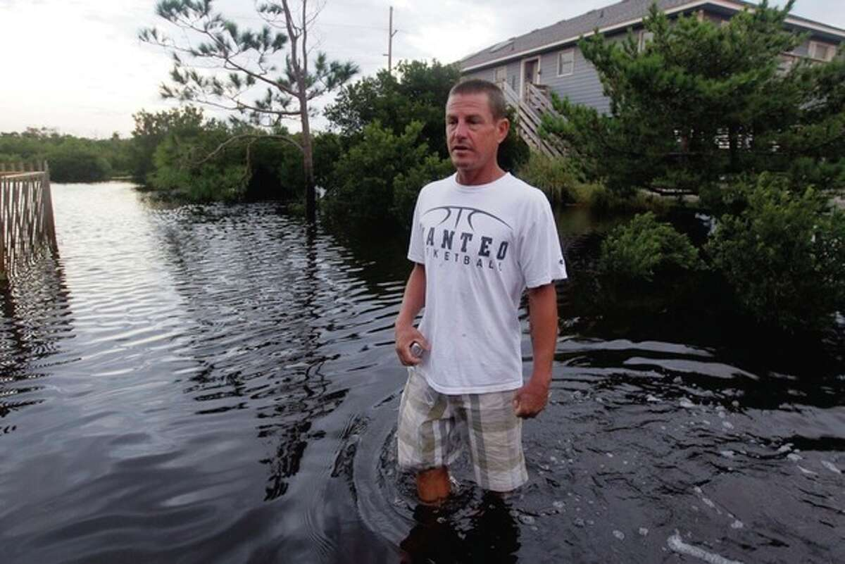 Steve Downing surveys the damage around his house from Hurricane Irene in Nags Head, N.C., Sunday, Aug. 28, 2011. The hurricane unloaded more than a foot of water on North Carolina, spun off tornadoes in Virginia, Maryland and Delaware, and left 3 million homes and businesses without power as it moved up the East Coast. (AP Photo/Gerry Broome)